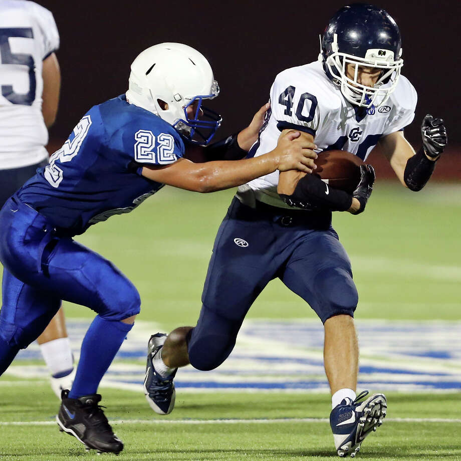 Central Catholic running back Thomas Palomera looks for running room around Lanier's Steve Torres last year. He's one of 26 returning lettermen to the Buttons. Photo: Express-News File Photo / © 2014 San Antonio Express-News