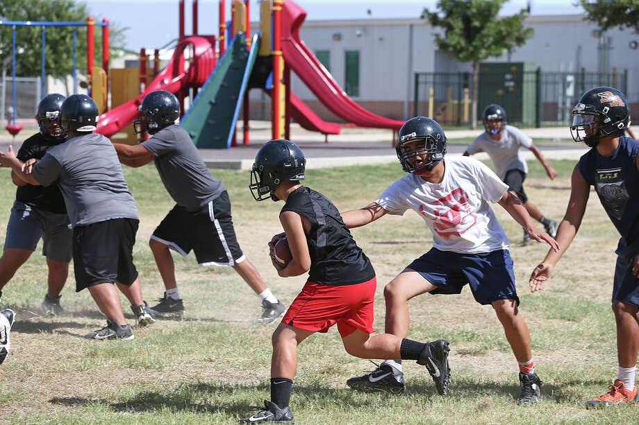 Playground equipment is a backdrop during practice last year at Brooks Academy. Its roster has been tightened from 60 to 30 players. Photo: Express-News File Photo