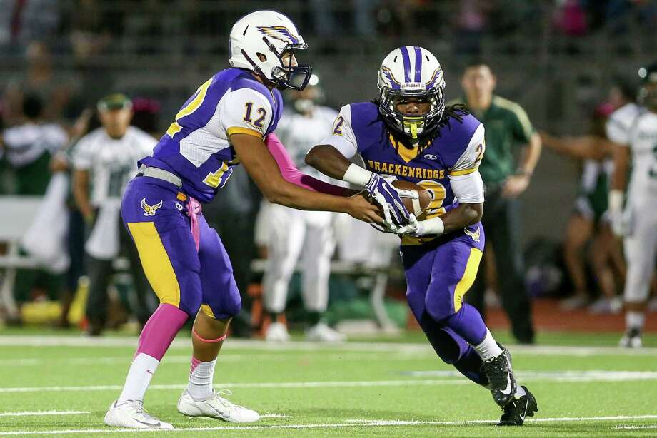Brackenridge's Trey Mathis (right) takes a handoff from Antonio Lopez on a 19-yard touchdown run during the first quarter of their game at Alamo Stadium on Thursday, Oct. 16, 2014. Brackenridge beat the Cowboys 44-28. Photo: Marvin Pfeiffer /San Antonio Express-News / Express-News 2014