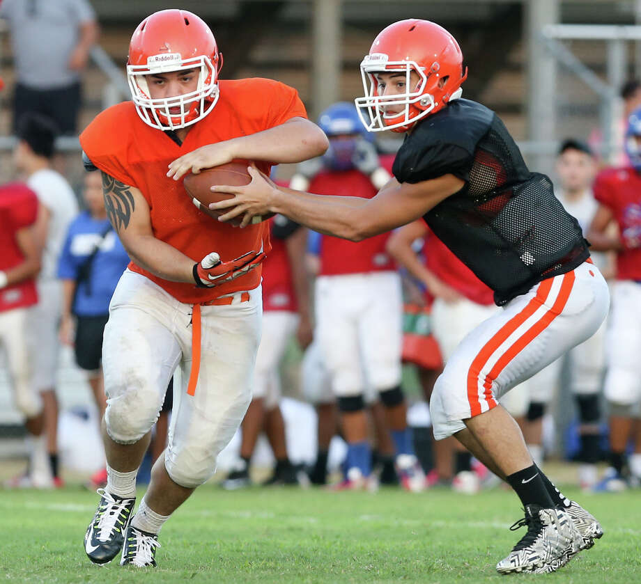 Burbank running back Devin Gusme (left)   takes a handoff from his brother, quarterback Dylan Gusme, during their team's recent scrimmage with Memorial at the SAISD Sports Complex. Photo: Marvin Pfeiffer / San Antonio Express-News / Express-News 2015
