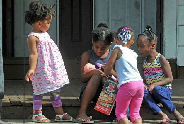 Four young girls play with a doll on an Ontario Street prch on Friday Aug. 28, 2015 in Albany, N.Y.  (Michael P. Farrell/Times Union) Photo: Michael P. Farrell