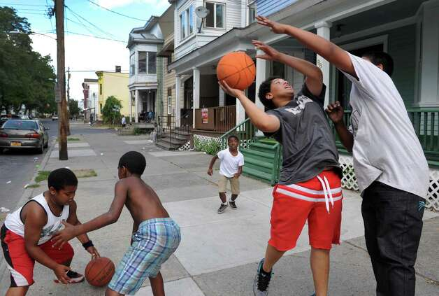 Fifteen-year-old Zack Headspeth drives to the hoop defended by 12-year-old Martin Montanez on Ontario Street Friday Aug. 28, 2015 in Albany, N.Y.  (Michael P. Farrell/Times Union) Photo: Michael P. Farrell