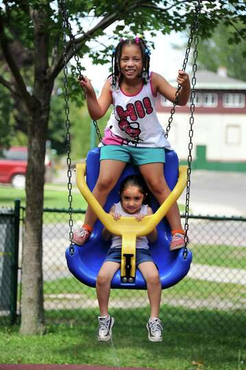 Anaya Torres, 7, of Schenectady, top, and her sister Alaysia Torres, 5, enjoy the beautiful day on t
