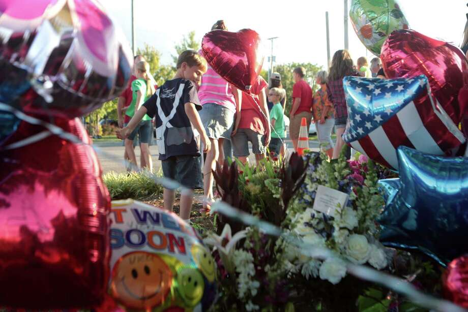 Conner Rothkopf, 7, of Salem, looks at the memorial for WDBJ7 shooting victims outside the WDBJ7 Digital Broadcast Center in Roanoke, Va. on Wednesday. The shooting of a television reporter and a cameraman unfolded on live TV before an audience of tens of thousands. Common sense rules could reduce gun-related homicides in the U.S. Photo: Heather Rousseau /Associated Press / HEATHER ROUSSEAU | The Roanoke T