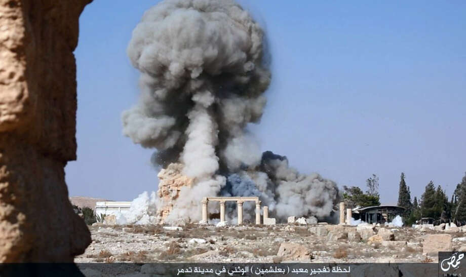 Smoke rises from a nearly 2,000-year-old temple in the Syrian city of Palmyra, the latest target of the Islamic State campaign against historic sites in Iraq and Syria. A reader compares the push to remove Conferedate monuments to the destruction in the Middle East. Photo: Uncredited /Associated Press / militant social media account