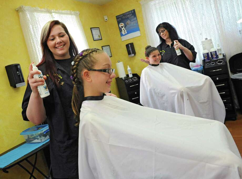 Mandee Slader, left, and her mother Helaina Slader demonstrate how they use a mint spray for the hair of a client that had lice on Tuesday, Aug. 25, 2015 in Ballston Lake, N.Y. The women run the business Miracles on Lice where they remove lice eggs from peoples' hair strand-by-strand. Kaitlyn Belfi, 12, left, and Jenna Slader, 12, are just the models for the photo, not clients. (Lori Van Buren / Times Union) Photo: Lori Van Buren / 00033116A