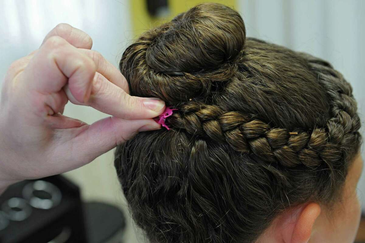 Helaina Slader demonstrates how she puts on clips after she braids the hair of a client that had lice on Tuesday, Aug. 25, 2015 in Ballston Lake, N.Y. Slader and her daughter Mandee Slader run the business Miracles on Lice where they remove lice eggs from peoples' hair strand-by-strand. (Lori Van Buren / Times Union)