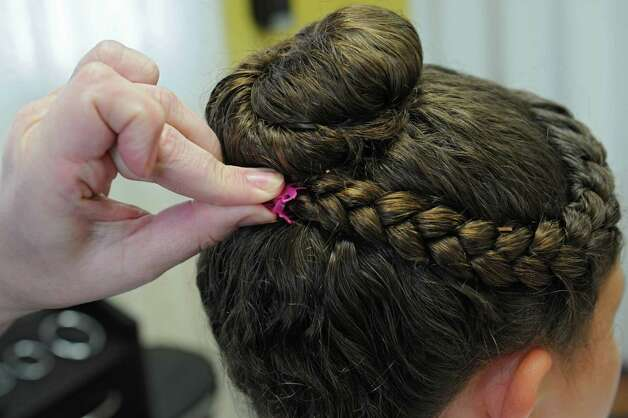 Helaina Slader demonstrates how she puts on clips after she braids the hair of a client that had lice on Tuesday, Aug. 25, 2015 in Ballston Lake, N.Y. Slader and her daughter Mandee Slader run the business Miracles on Lice where they remove lice eggs from peoples' hair strand-by-strand. (Lori Van Buren / Times Union) Photo: Lori Van Buren / 00033116A
