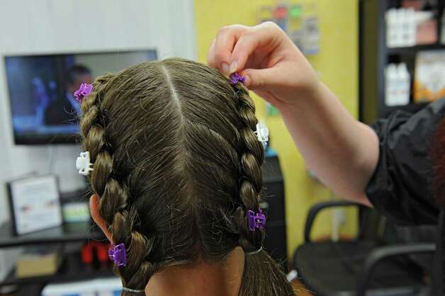 Mandee Slader demonstrates how she puts on clips after she braids the hair of a client that had lice on Tuesday, Aug. 25, 2015 in Ballston Lake, N.Y. Slader and her mother Helaina Slader run the business Miracles on Lice where they remove lice eggs from peoples' hair strand-by-strand. (Lori Van Buren / Times Union) Photo: Lori Van Buren / 00033116A