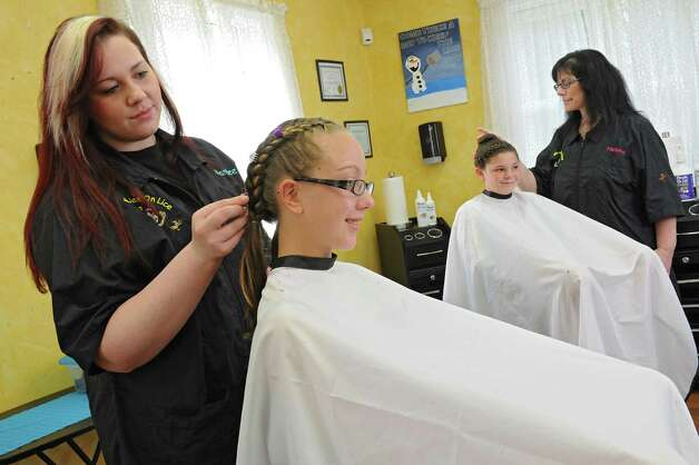 Mandee Slader, left, and her mother Helaina Slader demonstrate how they braid the hair of a client that had lice on Tuesday, Aug. 25, 2015 in Ballston Lake, N.Y. The women run the business Miracles on Lice where they remove lice eggs from peoples' hair strand-by-strand. Kaitlyn Belfi, 12, left, and Jenna Slader, 12, are just the models for the photo, not clients. (Lori Van Buren / Times Union) Photo: Lori Van Buren / 00033116A
