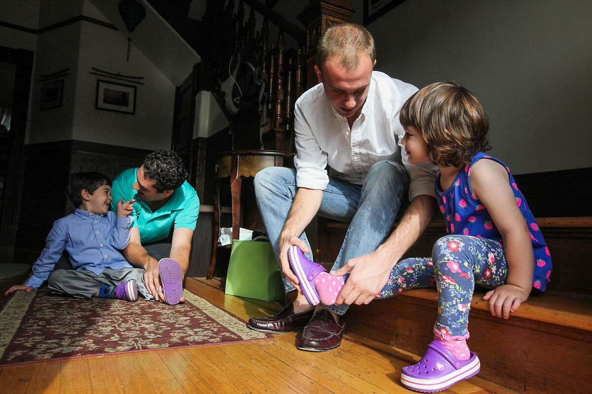 David Jacoby (second from left) helps son Max Jacoby put on his shoes and Brett Davis (center), and Airbnb guest helps Olivia Jacoby put on her shoes before school, in the Jacoby's home in San Francisco, California, on Friday, Aug. 28, 2015. Brett Davis, is a guest, who's staying in the Jacoby's Airbnb. Proposition F, the ballot initiative to rein in short-term rentals, would make it easier for neighbors to sue other neighbors, like the Jacoby's for hosting Airbnb guests.