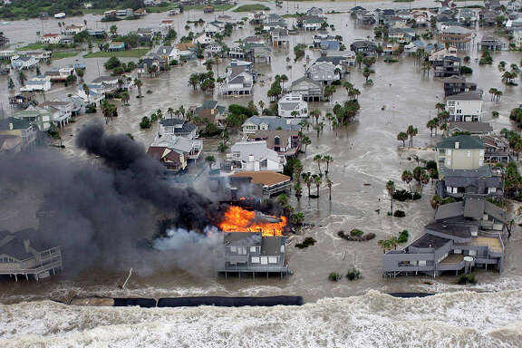 FILE - This Sept. 12, 2008, file photo shows fire destroying homes along the beach on Galveston Island, Texas as Hurricane Ike approaches in Galveston, Texas. Galveston, worried millions could be lost if Census shows post-Ike population drop, had asked Census officials to include in the city's population count residents who have temporarily moved off the island since the hurricane. But Census officials say they can't make an exception for natural disasters. (AP Photo/David J. Phillip, File)