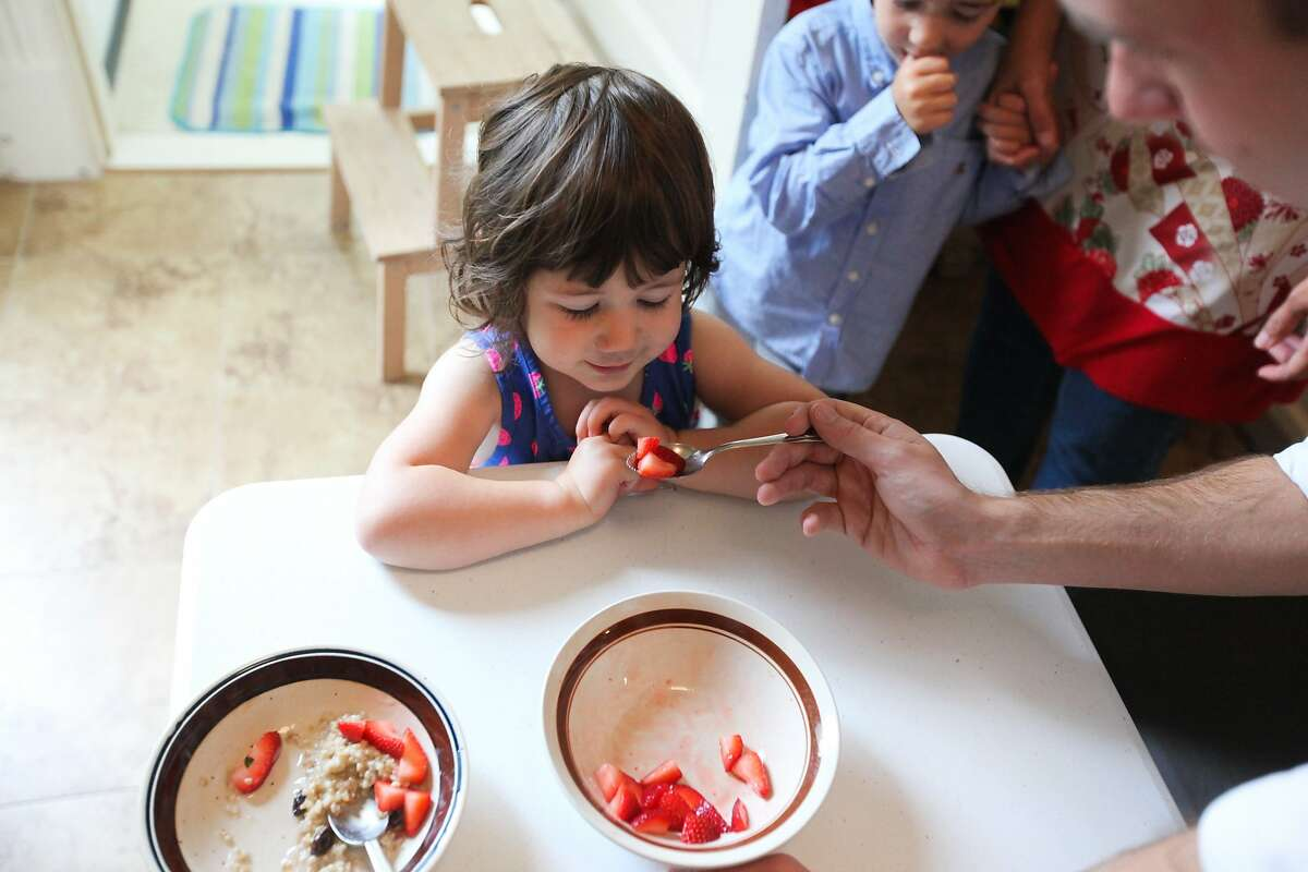 Brett Davis (right), an Airbnb guest, gives Olivia Jacoby, age 2, strawberries for her oatmeal in the Jacoby's kitchen in San Francisco, California, on Friday, Aug. 28, 2015. Brett Davis, is a guest, who's staying in the Jacoby's Airbnb. Proposition F, the ballot initiative to rein in short-term rentals, would make it easier for neighbors to sue other neighbors, like the Jacoby's for hosting Airbnb guests.