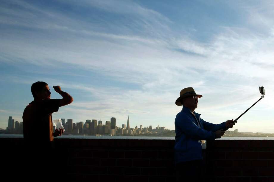 Tourists take photos on Treasure Island, where developers and San Francisco officials are planning to install public art and create a vibrant art community. Photo: Scott Strazzante / Scott Strazzante / The Chronicle / ONLINE_YES
