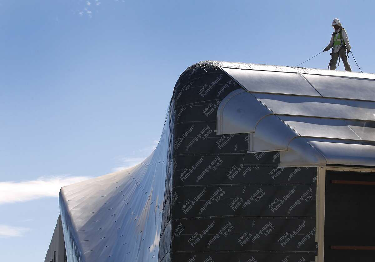 A construction worker works on the sloping steel roof of the new Berkeley Art Museum in Berkeley, Calif. on Friday, Aug. 28, 2015. Several multi-level residential and commercial development projects are changing the landscape of the downtown area.