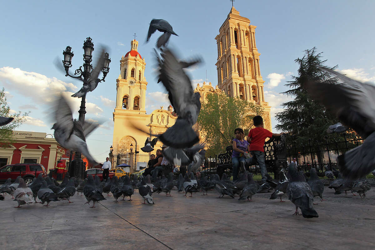 """People hang out at Plaza de Armas by the Santiago Cathedral in Saltillo, Mexico, Wednesday, Feb. 19, 2014. The state of Coahuila has a debt of almost $3 billion, an amount that is equal to its annual budget. Dubbed the """"megadeuda,"""" by the Mexican press, the blame is placed on the administration of the past governor Humberto Moreira."""