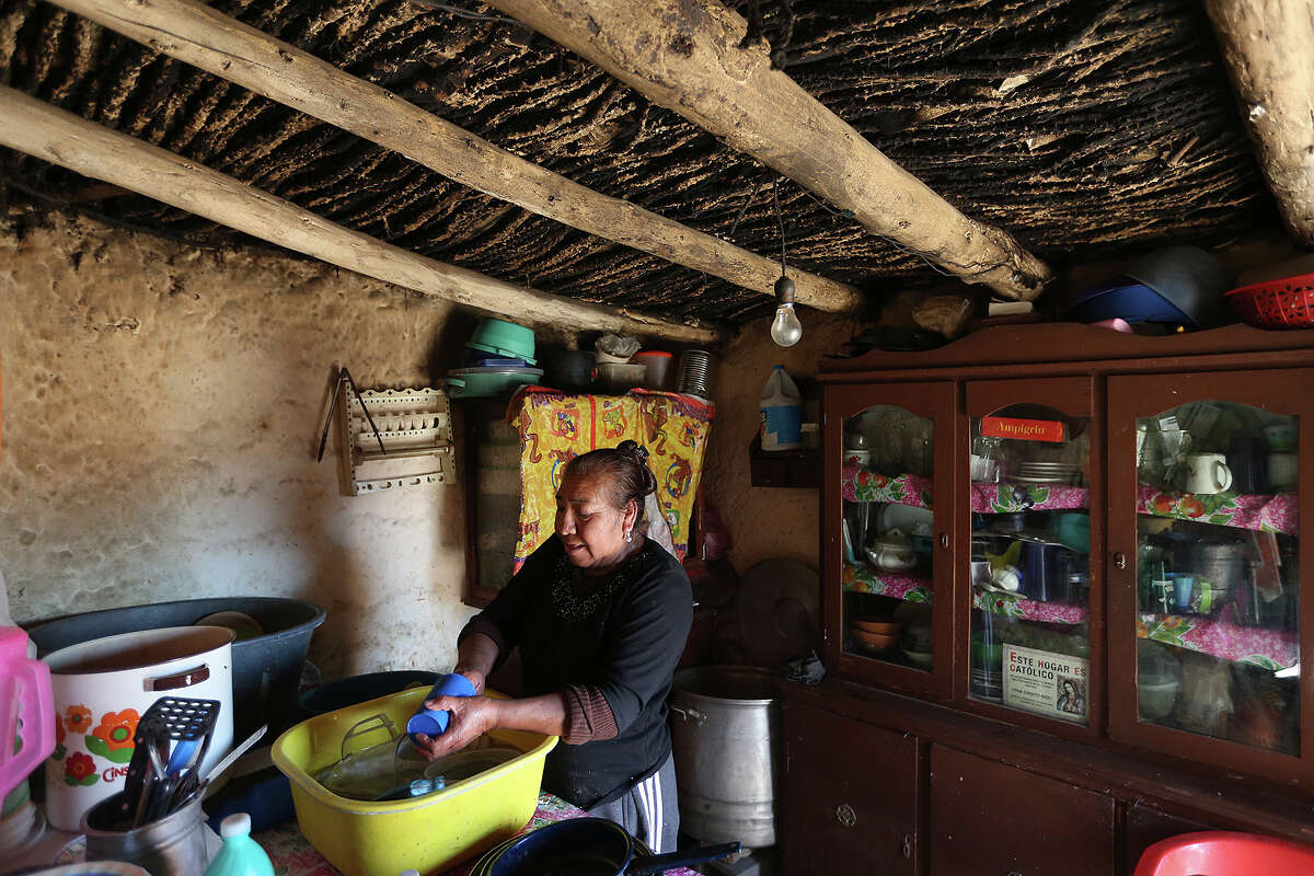 """Josefina Mata Jimenez, 58, washes dishes at her house in the ejido of Bu?-uelos, Coahuila south of Saltillo, Mexico, Tuesday, Feb. 18, 2014. The administration of former Governor Humberto Moreira racked up close to $3 billion in debt and as a result, the state has cut back in social services. Moreira, whose administration billed itself as, ?'El Gobierno de la Gente,?"""" or people?•s government, implemented various program such as the ?'people?•s card,?"""" ?'people?•s uniforms,?"""" and ?'people?•s shoes?"""". The cards were like food stamps, given out monthly, with dollar amounts ranging from $15 to $50. It was the only benefit that made it to the ejido and Mata said, ?'We lost a lot of benefits from the card?""""."""