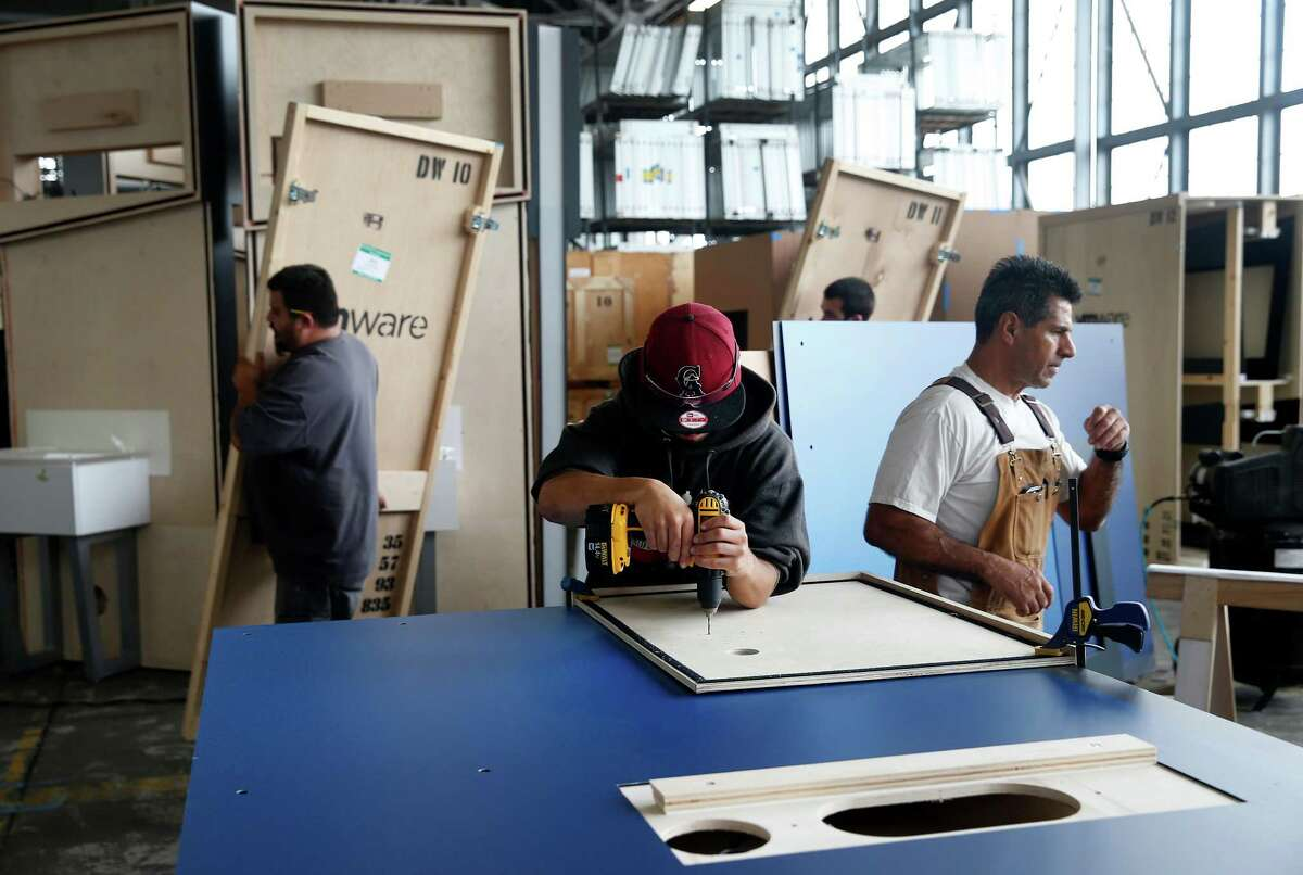 Ricky Diaz Jr. (center) works on a trade show display with his father (right) at the Group Delphi production warehouse in Alameda.