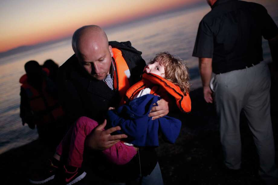KOS, GREECE - AUGUST 28:  A migrant family from Syria arrives as the sun rises on the beach on the island of Kos after crossing a three mile stretch of the Aegean Sea from Turkey August 28, 2015 in Kos, Greece. Migrants from the Middle East and North Africa continue to flood into Europe at a rate that marks the largest migration since World War II.  (Photo by Win McNamee/Getty Images) *** BESTPIX *** Photo: Win McNamee, Staff / 2015 Getty Images