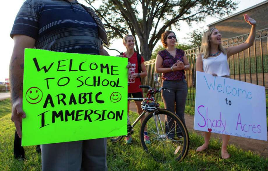 Supporters, from left to right, Kris Quiroz, Christy Lan, Allison Newport, and Kallie Benes, greet students and parents on the second day of school at the new Arabic Immersion Magnet School, Tuesday, Aug. 25, 2015, in Houston. Protests marred the first day of class for about 132 kindergarten and pre-K students at the Houston Independent School District's new school. (Cody Duty / Houston Chronicle) Photo: Cody Duty, Staff / © 2015 Houston Chronicle