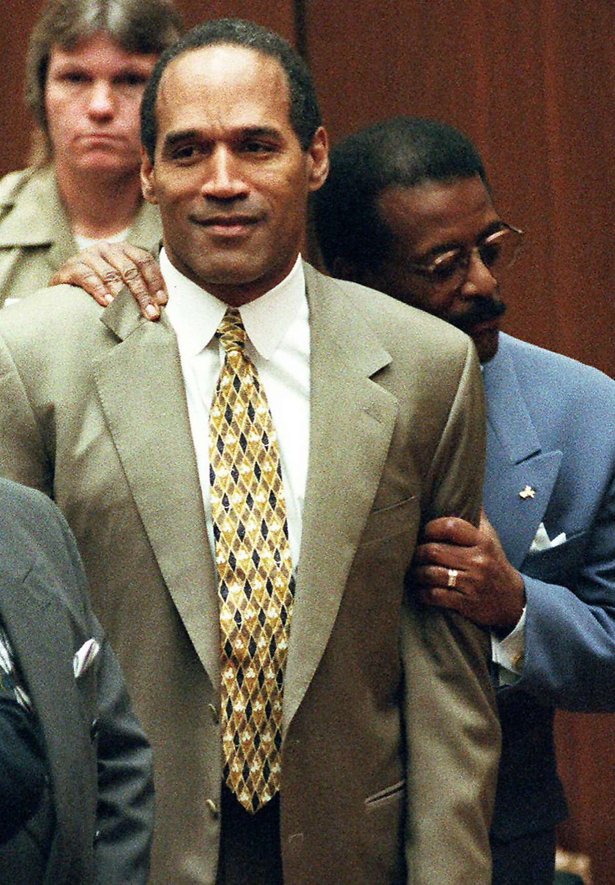 FILE - In this Oct. 3, 1995 file photo, attorney Johnnie Cochran Jr. holds onto O.J. Simpson as the not guilty verdict is read in a Los Angeles courtroom. Simpson's former manager has been ordered by a Los Angeles County judge Monday, June 15, 2009, to keep the former football star's so-called acquittal suit in storage until it is determined who rightfully owns it. (AP Photo/Pool, Myung J. Chun)