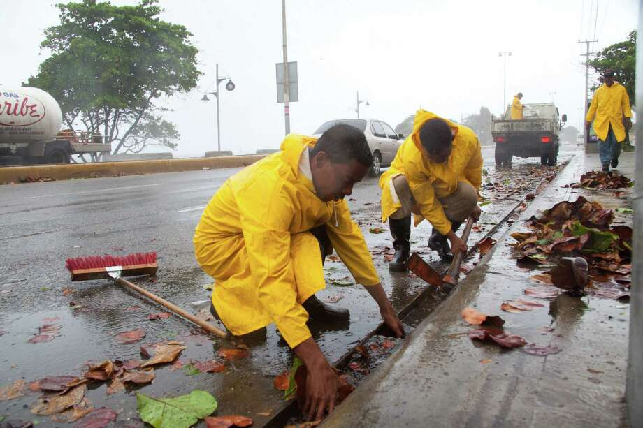 Workers clean highway gutters as Erika approaches Santo Domingo in the Dominican Republic. Photo: Tatiana Fernandez /Associated Press / AP