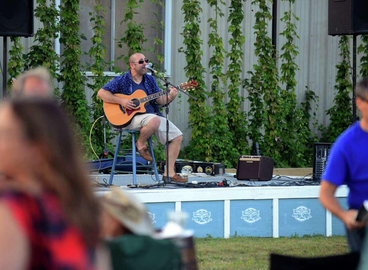 Two Roads Brewing Company held its Hopyard Concert Series event featuring guitarist Jon Slow opening the evening, pictured, and later Hitch and the Giddyup performed at the brewery in Stratford, Conn., on Friday Aug. 28, 2015. The brewery also featured its newest beer: Field Yield Pale ale, which was made with estate grown cascade and centennial hops. The hops were on prominent display along one end of the yard serving as a backdrop for the concert. Along with the new beer, there were food trucks, bocce ball and cornhole games set up.