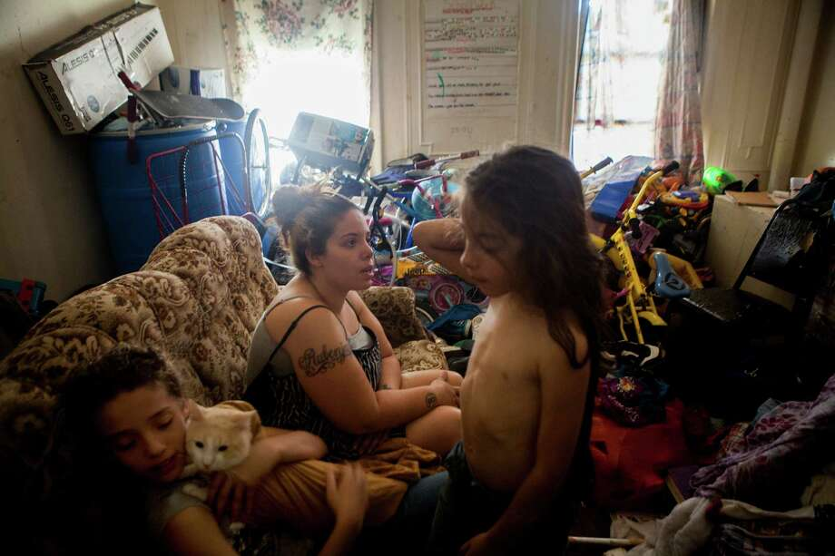 "Merlinda Fernandez, center, with her children in her apartment at 60 Clarkson Avenue in the Brooklyn borough of New York, July 16, 2015. Investigators ""observed these buildings to be run down, filthy, and often riddled with rats, mice and/or roaches,"" according to a report released in March by the Department of Investigation. (Sam Hodgson/The New York Times) ORG XMIT: XNYT70 Photo: SAM HODGSON / NYTNS"