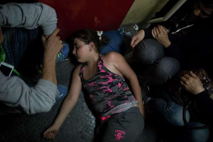 In this photo taken late Thursday, Aug. 27, 2015, migrants travel on an overnight train from the Mac