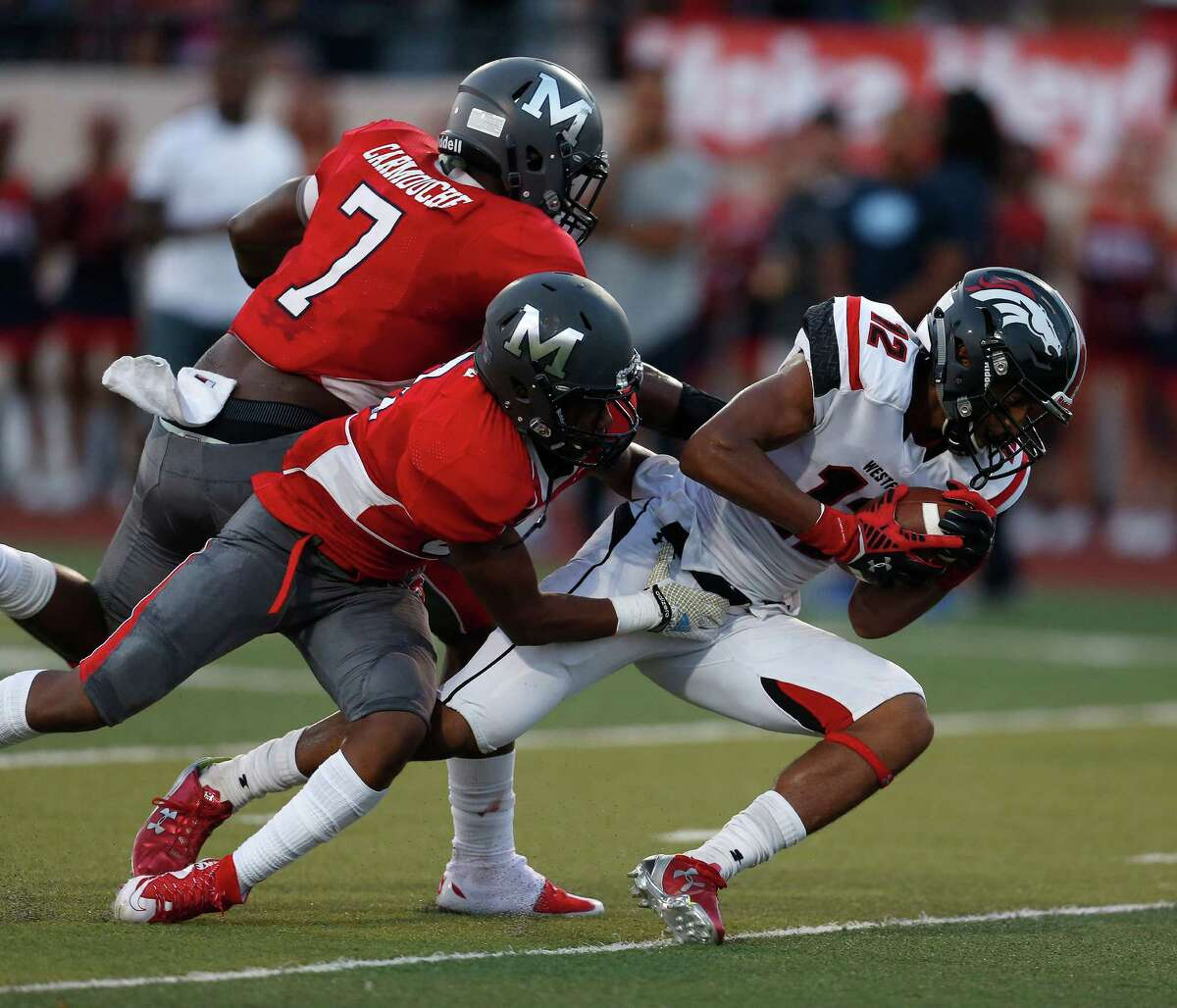 Wetfield's Lemuel Leblanc (12) scores a touchdown against Manvel's Brandon Bell (8) and Jordan Carmouche (7) during the first half of the Westfield vs Manvel High School football game on Friday, Aug. 28, 2015, in Alvin.