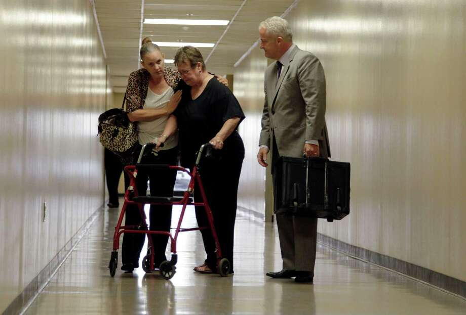 Joseph Hutcheson's widow, Nicole, consoles Hutcheson's mother, Ruth Boatner, on Friday as they are escorted out of a courts building by their attorney Scott Lidji after viewing jail footage in Dallas. Photo: Vernon Bryant, THE DALLAS MORNING NEWS / 20026314A