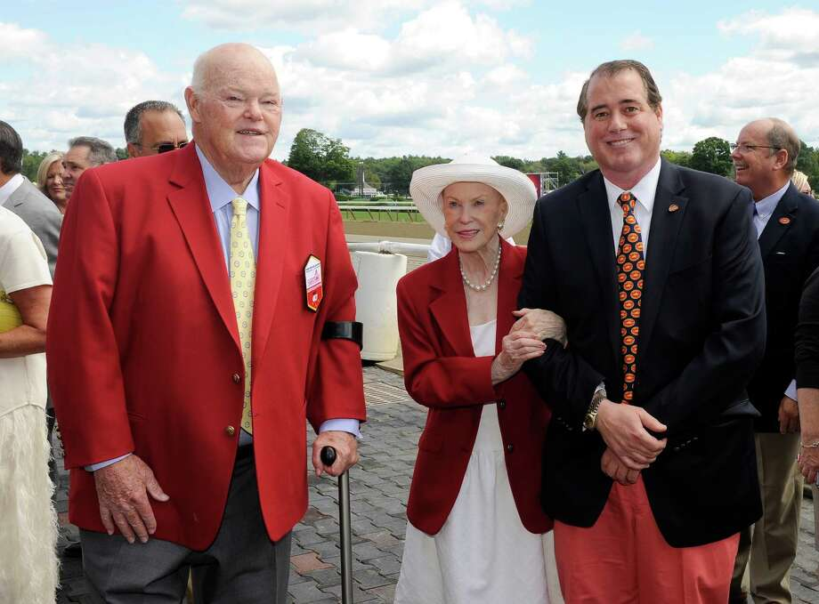 "The New York Racing Association 2015 inductees to the Saratoga Walk of Fame, Ogden Mills ""Dinny"" Phipps of Phipps Stable, left, and Marylou Whitney of Marylou Whitney Stables, center, escorted by her husband John Hendrickson, right, leave the the winners circle after being honored for their achievements during the annual Red Jacket Ceremony at Saratoga Race Course on Friday, Aug. 28, 2015, in Saratoga Springs, N.Y. (AP Photo/Hans Pennink) ORG XMIT: NYHP107 Photo: Hans Pennink / FR58980 AP"