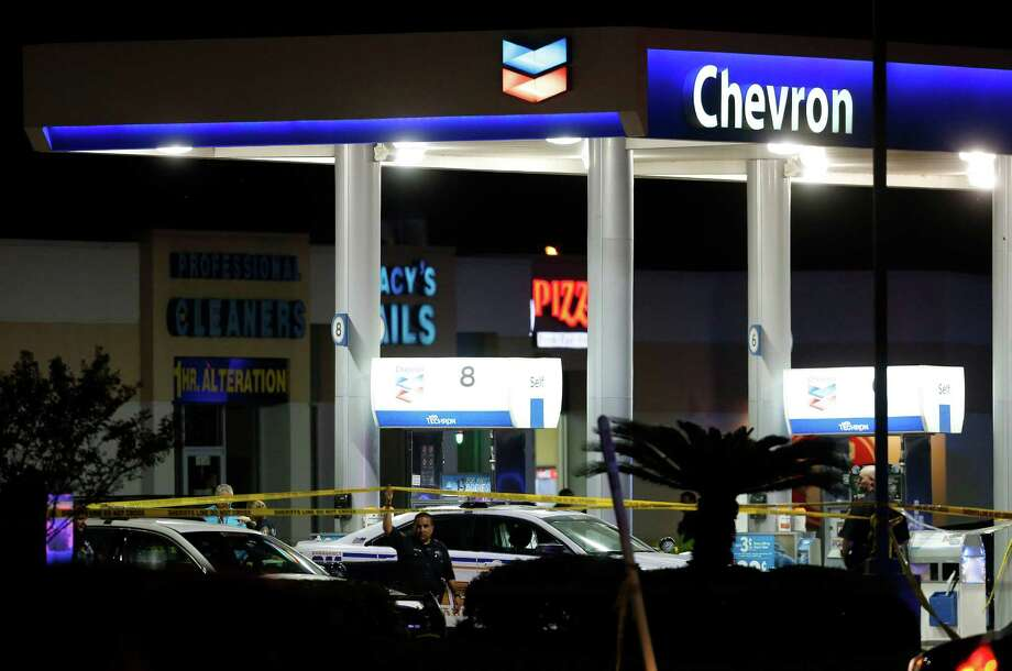 Officials investigate the scene where a deputy was ambushed by a gunman at a Chevron station at Telge and West in northwest Harris County on Friday night. Photo: Karen Warren, Houston Chronicle / © 2015 Houston Chronicle