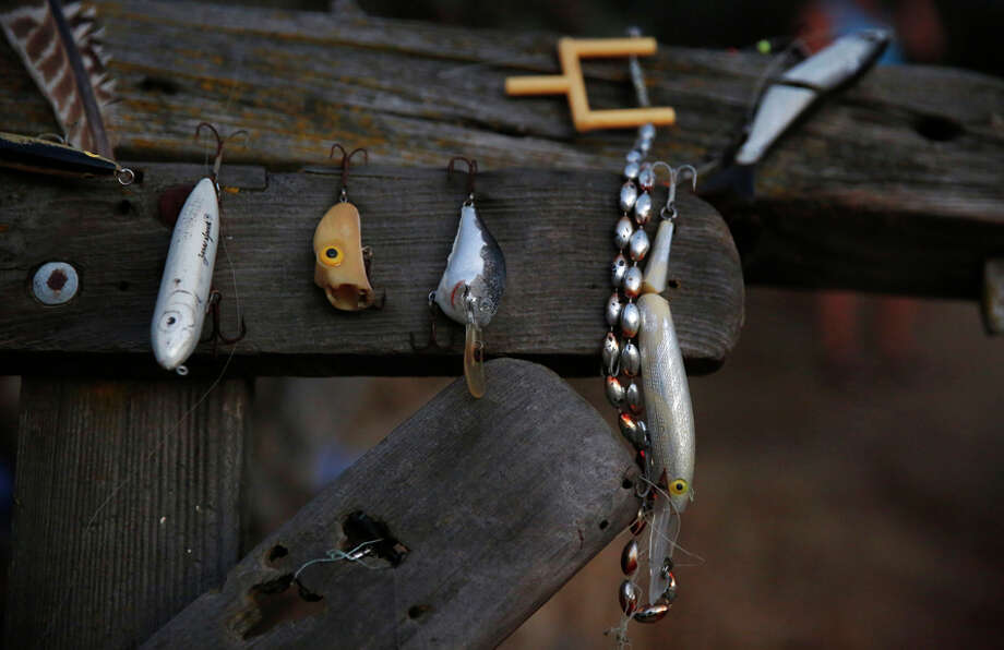 A collection of fishing hooks that Anita Lodge's family has found over the years hangs on display near her property. / ONLINE_YES