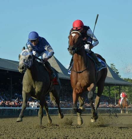 Texas Red with jockey Kent Desormeaux, right holds of Frosted ridden by Joel Rosario to win the 52nd running of The Jim Dandy Saturday evening Aug. 1, 2015 at the Saratoga Race Course  in Saratoga Springs, N.Y.      (Skip Dickstein/Times Union) Photo: SKIP DICKSTEIN