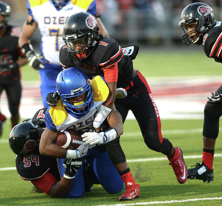Port Arthur Memorial's Brandon Jackson (left) and Kevin Williams put a stop to Ozen's Calvin Tyler during their Friday night match-up at Memorial Stadium in Port Arthur.  Photo taken Friday, August 28, 2015  Kim Brent/The Enterprise Photo: Kim Brent / Beaumont Enterprise