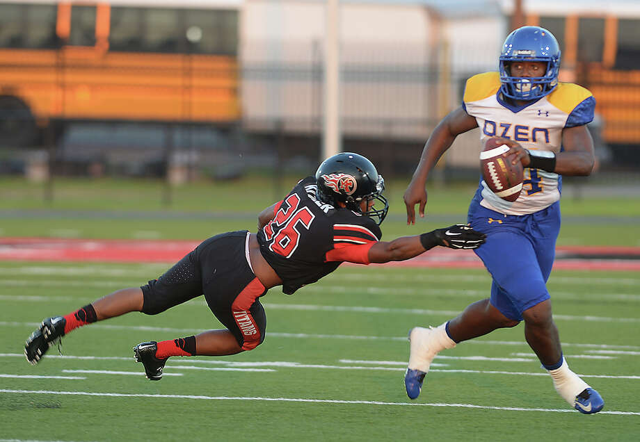 Port Arthur Memorial's James Kittler dives to try and bring down Ozen's Joshua Boyd during their Friday night match-up at Memorial Stadium in Port Arthur. Photo taken Friday, August 28, 2015 Kim Brent/The Enterprise Photo: Kim Brent / Beaumont Enterprise
