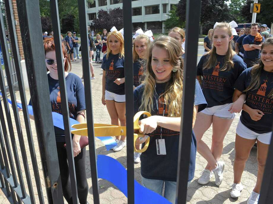 "Celia Cheyney, of Rocky Hill, was chosen to cut the ribon across the gate for Western Connecticut State University's ""Entering the Gate"" ceremony on the school's midtown campusn Danbury. Her father, Alaxander Cheyney, is a member of the WCSU class of 1997. The incoming freshman class symbolically and physically enter the campus through the wrought-iron gates on the midtown campus onFriday, August 28, 2015, in Danbury, Conn. Helping Cheyney is freshman Larissa Steinhauser, of Baltimore, MD. Photo: H John Voorhees III / Hearst Connecticut Media / The News-Times"