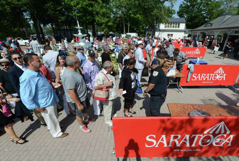 Spectators are searched prior to entering the Saratoga Race Course for Travers Day Saturday morning,