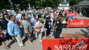 Spectators are searched prior to entering the Saratoga Race Course for Travers Day Saturday morning, Aug. 29, 2015, in Saratoga Springs, N.Y. (Will Waldron/Times Union)