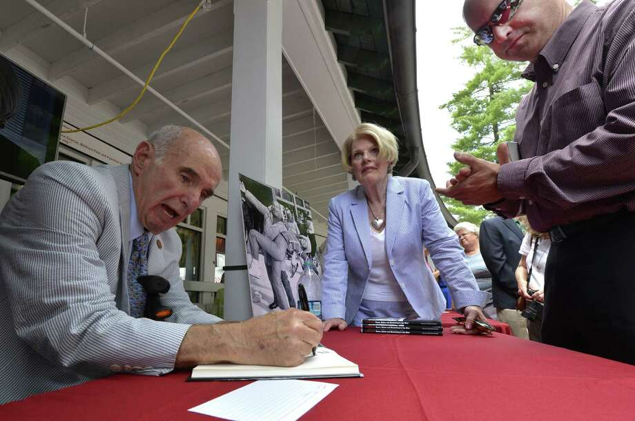 Master of marketing Ed Lewi, left signs his book of memories Wednesday afternoon Aug. 20, 2014,  at the Saratoga Race Course in Saratoga Springs, N.Y.  With Lewi is his wife Maureen , center.  (Skip Dickstein/Times Union) ORG XMIT: MER2014082015284091 Photo: SKIP DICKSTEIN