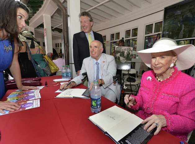 Ed Lewi signs his book of marketing memories  and is joined by his friend Mary Lou Whitney, right, Wednesday afternoon Aug. 20, 2014,  at the Saratoga Race Course in Saratoga Springs, N.Y.    (Skip Dickstein/Times Union) ORG XMIT: MER2014082015284692 Photo: SKIP DICKSTEIN