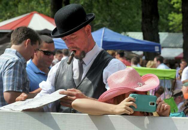 Joseph Coelho of Boston with his daughter 11-year-old Jane Coelho watch as the horses head to the paddock on Travers race day at Saratoga Race Course on Saturday Aug. 29, 2015 in Saratoga Springs, N.Y.  (Michael P. Farrell/Times Union) Photo: Michael P. Farrell / 00033156A