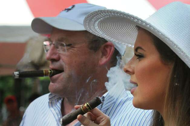 John Cahill of Delaware smokes a cigar with his daughter Christine Cahill on Travers race day at Saratoga Race Course on Saturday Aug. 29, 2015 in Saratoga Springs, N.Y.  (Michael P. Farrell/Times Union) Photo: Michael P. Farrell / 00033156A