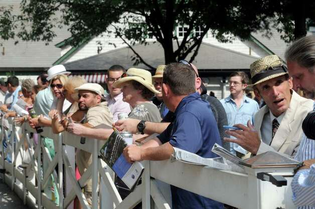Race fans watch as horses head to the paddock on Travers race day at Saratoga Race Course on Saturday Aug. 29, 2015 in Saratoga Springs, N.Y.  (Michael P. Farrell/Times Union) Photo: Michael P. Farrell / 00033156A