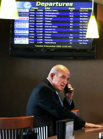 Ed Lewi makes a phone call beneath a Departures sign at the Albany County Airport December 8, 2009.  (John Carl D'Annibale / Times Union) ORG XMIT: MER2015082914214413 Photo: John Carl D'Annibale