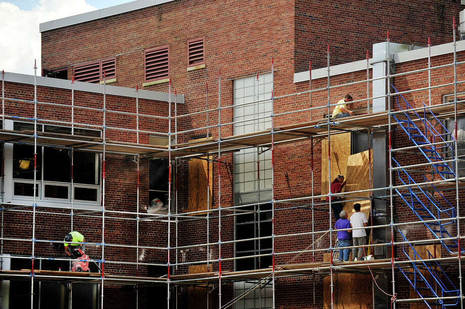 Workers work on Dolan Middle School earlier in August. Photo: Jason Rearick / Hearst Connecticut Media / Stamford Advocate