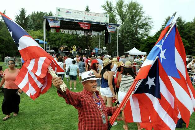 Nestor Rentas of the Bronx, center, peddles his native Puerto Rican flags during the Albany LatinFest on Saturday, Aug. 29, 2015, at Washington Park in Albany, N.Y. LatinFest celebrates the Hispanic cultural heritage and the contributions made by Hispanic Americans. (Cindy Schultz / Times Union) Photo: Cindy Schultz / 00033166A