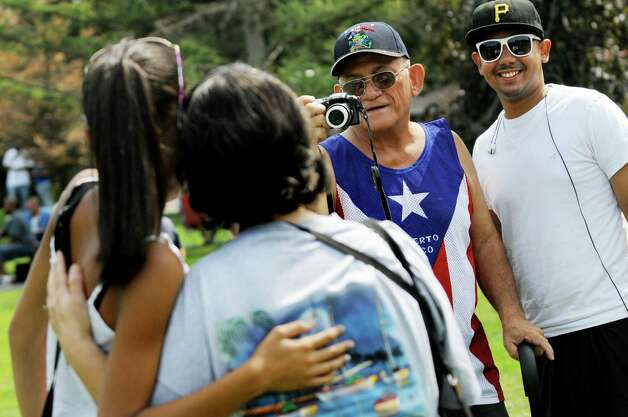 Puerto Rican native Aude Rivera of Albany, center, joined by his nephew Moses Berberena, right, takes a picture of his niece Rebeca Poche, 13, left, and his wife Margie Rivera during the Albany LatinFest on Saturday, Aug. 29, 2015, at Washington Park in Albany, N.Y. LatinFest celebrates the Hispanic cultural heritage and the contributions made by Hispanic Americans. (Cindy Schultz / Times Union) Photo: Cindy Schultz / 00033166A