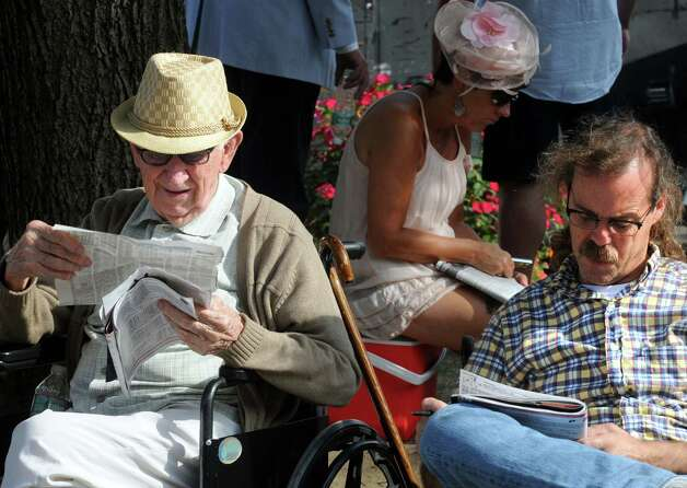 Paul Davis, right, of Blacstone, Mass., looks over the racing shheets with his grandfather 98-year-old Harold Erickson, who has been coming to Saratoga race Course for 70-years, on Travers race day on Saturday Aug. 29, 2015 in Saratoga Springs, N.Y.  (Michael P. Farrell/Times Union) Photo: Michael P. Farrell / 00033156A